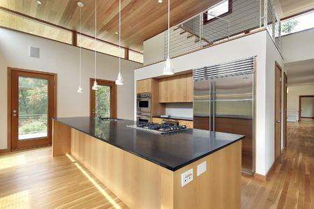Keuken in ultra moderne huis met zwart granieten eiland Stockfoto