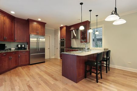 Kitchen in luxury home with cherry wood cabinetry photo