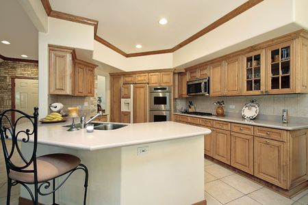 cabinetry: Kitchen in suburban home with oak wood cabinetry Stock Photo