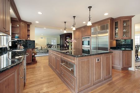 kitchen cupboard: Kitchen in luxury home with black marble countertops