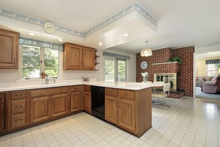 Kitchen in suburban home with brick fireplace photo