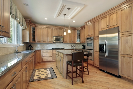 kitchen island: Kitchen in luxury home with wood cabinetry