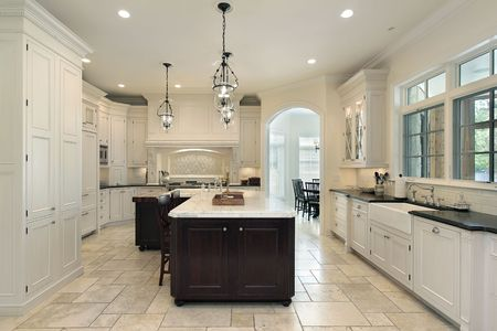 Luxury kitchen in suburban home with white cabinetry photo