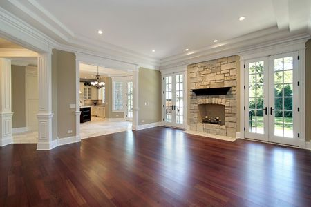 hardwood: Living room in new construction home with stone fireplace