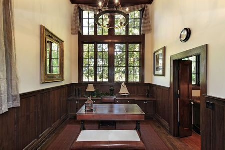 Office in luxury home with dark wood paneling