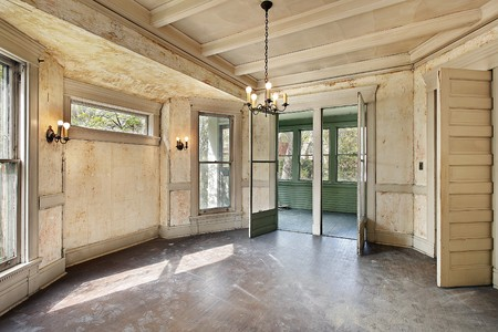 Dining room with peeling paint in old abandoned home