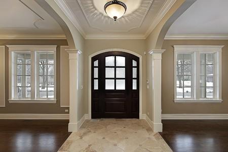 新建設のマホガニーの木製のドアと家の玄関