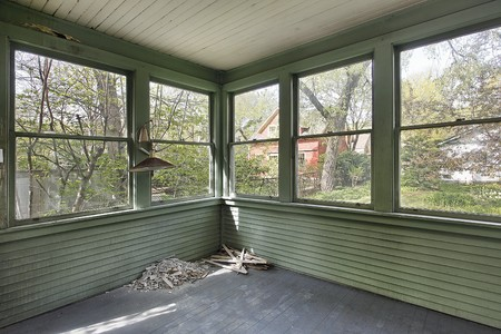 Green porch with wall of windows in old abandoned home photo