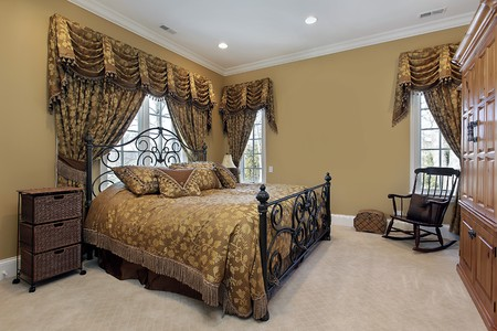 Master bedroom in luxury home with gold walls photo