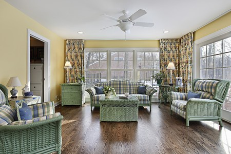 Sun room in suburban home with green wicker furniture