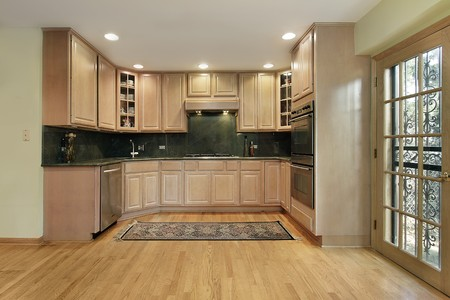 Kitchen in remodeled home with oak wood cabinetry photo
