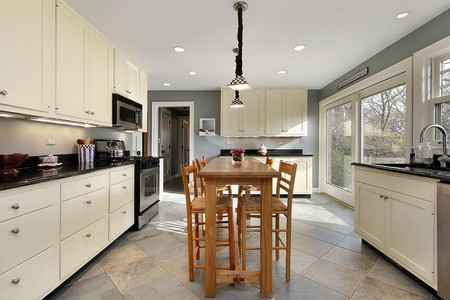 cabinetry: Kitchen with white cabinetry and wooden table