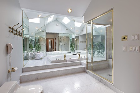 Master bath in luxury home with mirrored tub area photo