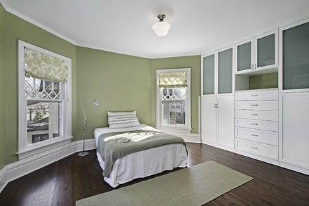 Hoofd slaap kamer met groene muren en donkere houten vloeren