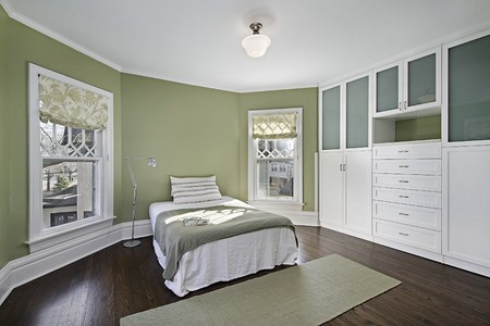 Master bedroom with green walls and dark wood flooring Stock Photo