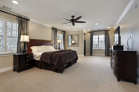 family  room: Master bedroom in luxury home with dark wood furniture Stock Photo