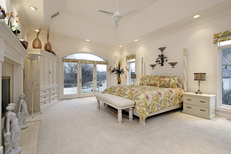 Master bedroom in luxury home with white fireplace photo