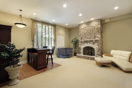 furnishings: Basement in luxury home with brick fireplace Stock Photo