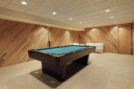 Pool table in suburban home with wood paneling