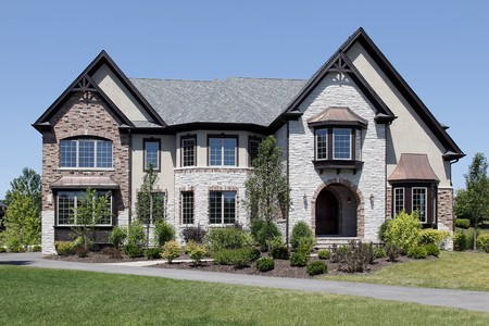 wood lawn: Luxury stone and brick home with arched entry