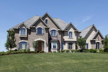 Grote bak stenen huis met stenen ingang en houten deur  Stockfoto