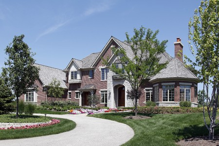 Large brick home in suburbs with stone entry photo