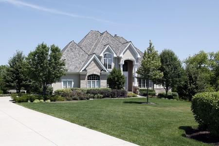 Grote bak stenen huis met gebogen ingang en cedar dak
