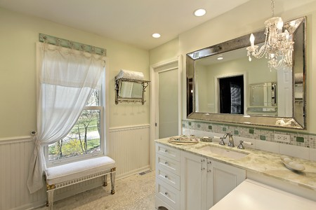 Bathroom in luxury home with white cabinetry photo