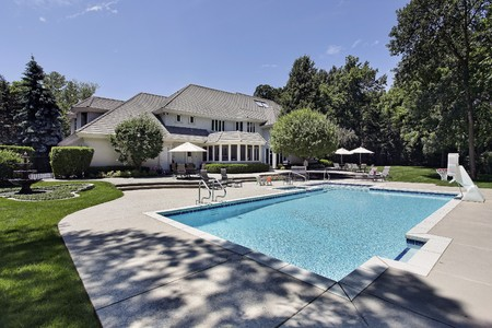 Swimming pool and deck in back of luxury home photo