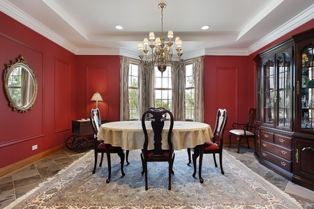 dining table and chairs: Dining room in luxury home with red walls Stock Photo