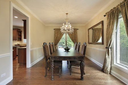 home furniture: Dining room in suburban home with gold draperies