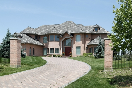 Luxury brick home with pillars and arched entry photo