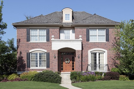 Brick home with wood door and front balcony photo