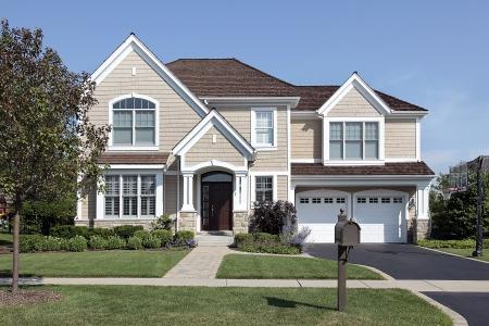 paisajismo: Casa en los suburbios con la entrada de arco y el techo de cedro color marr�n