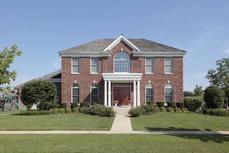 Large brick home with white columns and front balcony Stock Photo - 10293052