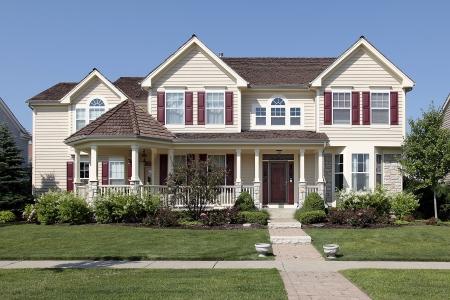 Grote voorstedelijk huis met gele gevelbeplating en rode luiken Stockfoto