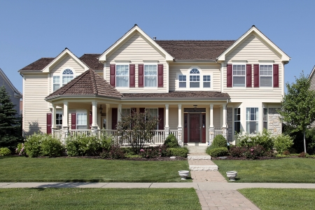 Large suburban home with yellow siding and red shutters