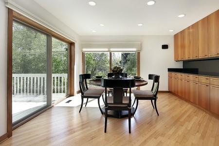 lighting fixtures: Breakfast room in luxury home with door to deck Stock Photo