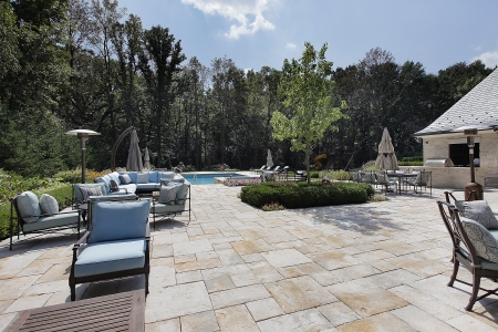 Large stone patio of luxury home with swimming pool