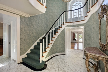 second floor: Foyer with green stairs and second floor round window Stock Photo