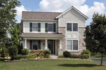 Huis met stenen front en groene luiken