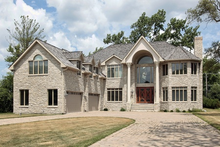 Large new construction stone home with arched entry photo