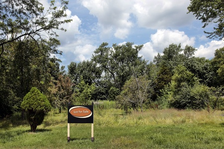 Vacant land in suburbs with Lot for Sale sign photo