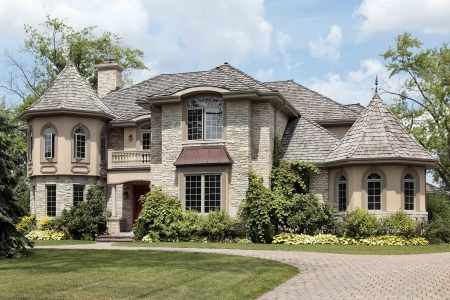 custom home: Luxury stone home with turret and cedar shake roof