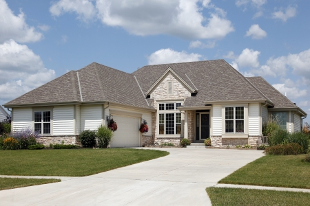 Home with stone entry and cream colored siding photo