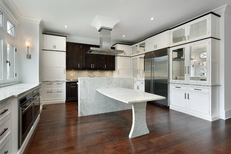 Modern kitchen with white cabinetry and granite island photo