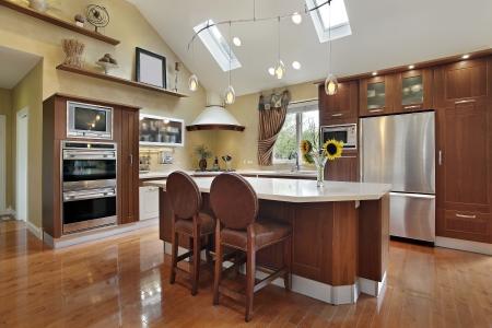 レッドウッドのキャビネットと中央の島の高級キッチン
