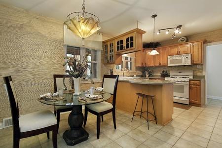 familia cenando: Cocina con gabinetes de madera y �rea de comer