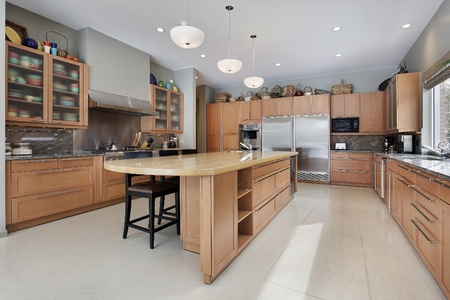 Large kitchen in luxury home with oak wood cabinetry photo