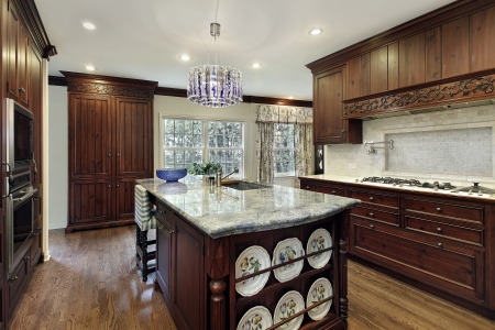 modern dining room: Traditional kitchen with dark wood cabinetry and granite island Stock Photo